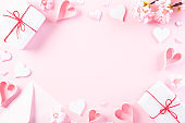 Pink paper hearts with gift box on Light pink pastel paper background. Love and Valentine's day concept.