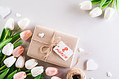 International Women's Day concept. Woman lace lingerie jewelry perfume present with white tulips and paper tag text on soft fabric gray background. flat lay, March 8.