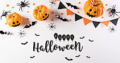 Halloween decorations made from pumpkin, paper bats and black spider on white background. Flat lay, top view with Happy Halloween text.