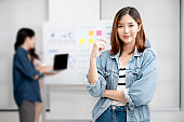 Young women asian confidence team leader business looking camera and smile in modern office room with blurred background group people