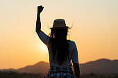 Soft focus of woman with fist in the air during sunset sunrise mountain in background. Stand strong. Feeling motivated, freedom, strength and courage concept.