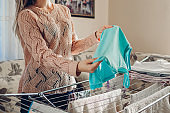 Young woman housewife hanging clean clothes on dryer after washing at home. Housekeeping and household chores