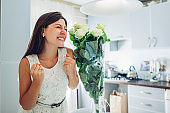 Valentine's day present. Happy young woman found bouquet of roses flowers on kitchen. Women's day