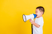 Asian Thai happy portrait cute little cheerful child boy holding and shouting or screaming through the megaphone her looking to side, studio shot isolated on yellow background with copy space
