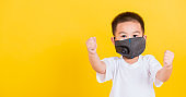 Asian Thai happy portrait cute little cheerful child boy wearing mask protective for covid-19 or pm2.5 dust he raise hands glad excited cheerful after recovering from illness, on yellow background