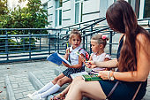Happy mother kids daughters spend time together after classes. Children reading books outdoors primary school.
