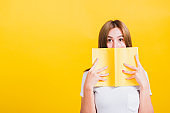 woman stands holding yellow book or diary