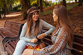 Outdoor portrait of two young women talking sitting on bench in autumn park. Friends hang out together.