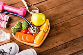 fresh organic fruits and vegetables in heart plate wood and sports equipment and doctor stethoscope