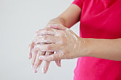 Woman washing hands with soap for COVID-19 corona virus prevention concept