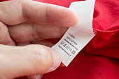 Hand hold and reading at white laundry care washing instructions clothes label on red cotton shirt