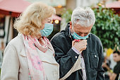 Senior couple walking hand in hand with protective mask