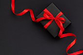 Black Friday concept. Top view of black gift box with red ribbon on black and red background with copy space for text.