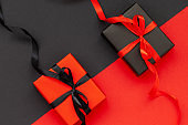 Black Friday concept. Black gift box with red ribbon and red present box with black ribbon. Flat lay