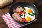 fried egg bacon champignons tomato parsley in a pan wooden