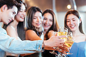 Focus on hand .group of Asian friends having party with hand holding wine glass toasting at outdoor restaurant. drinking alcohol, young people night lifestyle. positive emotion and friendship concept