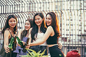 Group of Asian girl having party with hand holding beer bottle toasting at outdoor restaurant. drinking alcohol, young people night lifestyle. positive emotion and friendship concept. copy space