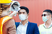 Female worker scanning fever temperature with digital thermometer construction site staff wearing hygiene face mask protect from Coronavirus or COVID-19. New Normal working life adaptation in 2020