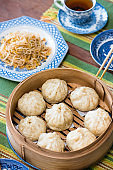 Steamed meat stuffed buns in bamboo steamer with antique blue williow tableware