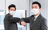 Portrait of Asian employee man in surgical face mask elbow bump greeting in New Normal lifestyle with colleague keep social distancing to prevent Coronavirus at office.  business meeting concept