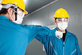 Asian male factory worker in medical face mask elbow bump greeting in New Normal lifestyle with colleague for social distancing to prevent Coronavirus, healthcare for industrial people. men at work