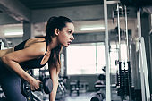 Side view of Caucasian fitness sporty woman lifting dumbbell for fit and firm bodybuilding stronger body. people lifestyle to workout exercise at gym. body fit motivation and healthy sport concept