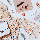Fashion female clothes and accessories for beach destinations or summer vacation. Flat lay with woman white clothing, straw hat and purse, make up on white background, woman travel fashion concept