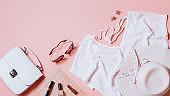 Fashion female clothes and accessories for beach destinations or summer vacation. Flat lay with woman white clothing, straw hat and purse, make up on pink background, woman travel fashion concept