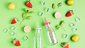 Flat lay with ingredients for summer refreshing drink or smoothie, ice cubes, herbs and glass jars on green background, top view, web banner. Strawberry, lime, ice and basil for summer cocktail
