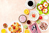 Continental breakfast with cereal, fried eggs, croissants, fruits and drinks on textured table, copy space. Table top with various healthy snacks and foods on rustic background