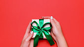 Woman presenting gift with green ribbon on lush lava color background, copyspace. Valentine's Day or Mother's Day greeting card in trendy colors, top view