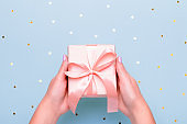 Woman hands holding gift box in pink color on pastel blue background with heart shape confetti, copyspace. Valentine's Day greeting card in trendy colors, Happy Valentine Day background