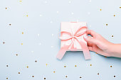 Woman holding gift box in pink color on pastel blue background with heart shape confetti, copyspace. Valentine's Day, Women's Day or Mother's Day greeting card in trendy colors
