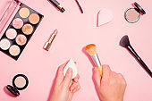 Woman holding make up brush and beauty sponge in hands, tools for makeup foundation. Beauty flat lay on pink table top with beauty products around.