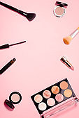 Flat lay with make up products in minimal style on pink desk. Frame with black mascara, lipstick, eyeshadow palette, different make up brushes. Top view, copy space.