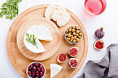 Traditional Spanish cuisine appetizers with white brie cheese, figs, olives and rose wine on white table top