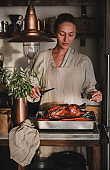 Woman carving roasted duck for Thanksgiving or Christmas holiday