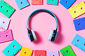 Painted audio cassettes in bright colors and blue earphones on pastel background, copy space, top view. Retro musical background. Retro audio tape cassettes, 80s background, pastel retro flat lay
