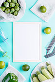 White board to write a plan or list with zero waste cotton bags, glass jars, metal straws reusable, fruits on blue table top, copy space. Zero waste lifestyle or sustainable lifestyle concept