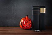 Book stack with scary pumpkin lantern, Halloween decor against grey stone background, copy space