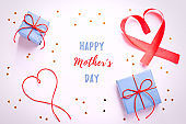 Happy Mother's Day greeting card with red hearts, blue gift boxes and golden confetti on pastel table top, overhead shot. Background for Mothers Day holiday with text
