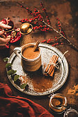 Human hand pouring cinnamon to turkish hot drink salep