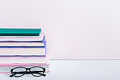 Stack of books on bookshelf with reading glasses against pink wall, still life, copy space. Home interior with books, reading concept