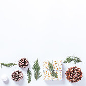 Wrapped presents with cedar and cones on white background. Preparation for Christmas holiday concept, christmas border, copy space, square format