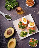 Healthy toasts with smoked salmon and avocado served with mustard, eggs and leafy greens on black table top. Mediterranean diet snack, open sandwich