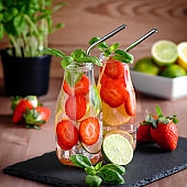 Refreshing drink or water with strawberry, citrus fruits lemon, lime and basil in mason jar with reusable metal straws. Healthy lemonade drink in glass jar, zero waste concept, sustainable lifestyle