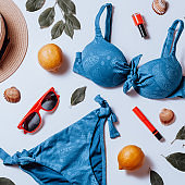 Classic blue bikini, red sunglasses, straw hat, fruits and leaves on white. Vacation woman accessories flat lay, top view