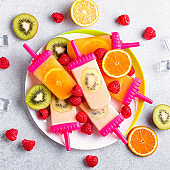 Summer refreshing homemade popsicles with oranges and kiwi. Healthy snack with fruits and frozen juice for summer heat on concrete table top, flat lay, copy space