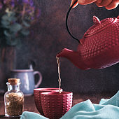 Woman holding pink teapot and pouring herbal chamomile tea in cups against dark background, square format. Chinese pink tea set with tea infusion on dark backdrop