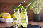 Refreshing drink or water with citrus fruits lemon and lime and basil herb in mason jar with reusable metal straws. Healthy lemonade drink in glass jar, zero waste concept, sustainable lifestyle